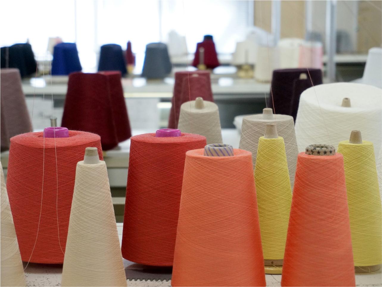 工場内にはさまざまな色の糸と大きなニットの編み機が80台ほど並ぶ