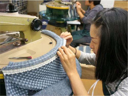 一目ずつニットの網目に針を通して縫い上げる繊細な工程を手作業で行う