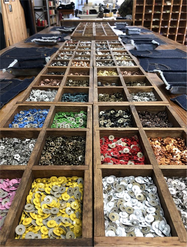 体験工房では、スキニーなどのジーンズのタイプ選びからスタート。好みのボタンを1つ、リベットを6つ選ぶのに悩むのも楽しい