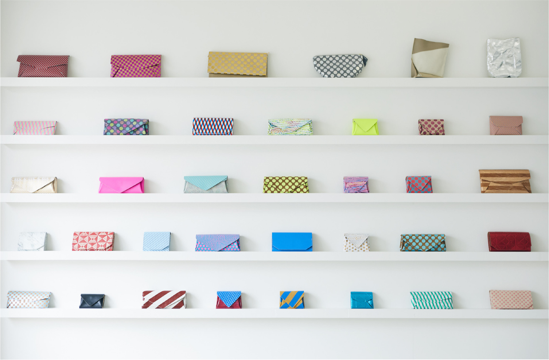 財布からポーチ、バッグとオリジナルレザーを使った商品が並べられた壁はかわいいの一言