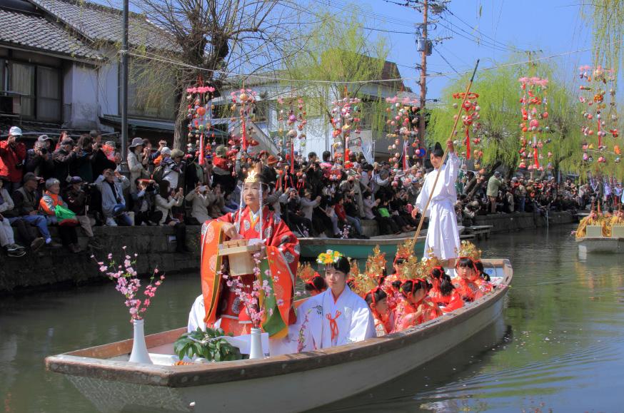 水上に飾られたさげもんの間を、稚児衣装を身にまとった子どもたちが舟で進む水上パレード